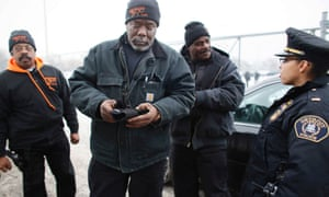 Armed volunteers from the crime-fighting community organisation known as Detroit 300 with a police lieutenant. Photograph: Angela Catlin