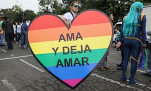 "A man carries a heart that reads in Spanish ""Love and let love"" at a gay pride parade in Lima, Peru."