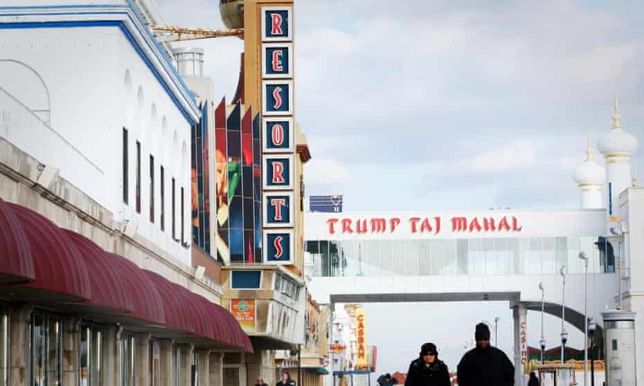 People walk along the boardwalk near the Resorts Atlantic City casino, left, in Atlantic City, New Jersey,.