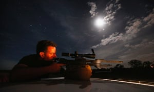 A kangaroo shooter, Steven O'Donnell, rests his .223 calibre rifle on the roof of his truck.