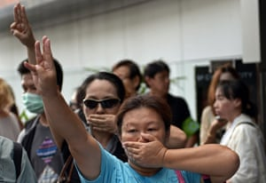 Anti-coup protesters flash a three-finger salute during a gathering at a shopping mall which was broken up by security forces in downtown Bangkok. Opponents of the coup are risking arrest by flashing the three-finger salute from The Hunger Games to defy a junta that has banned all public protests.