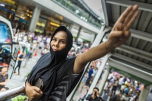 A woman holds up a salute during a protest against the coup at Terminal 21, a popular shopping mall in Bangkok. The salute is said to symbolise admiration and thanks and is shown as a farewell to loved ones. In this case, the loved one is reportedly Thai democracy.
