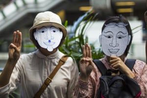 Two masked demonstrators show their support for the protests.