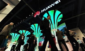 People walk past the Huawei booth