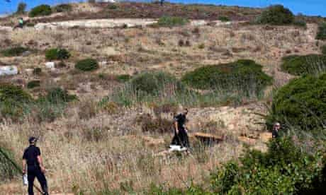 Detectives searching for Madeleine McCann work with a sniffer dog at an area in Praia da Luz