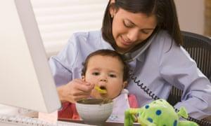 Hispanic mother feeding daughter and working Hispanic mother feeding daughter working
