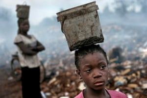 Fati, aged 8, works with other children searching through hazardous waste on an e-waste dump in Accra, Ghana.  Balancing a bucket on her head containing the metal she has found, tears stream down her face as the result of the pain from malaria.