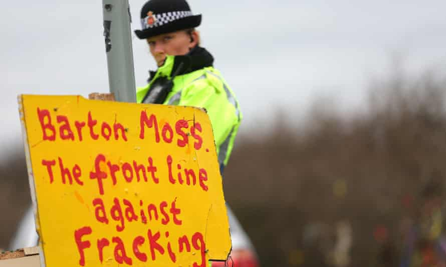 A police officer stands next to a sign as she watches protesters march towards the gates of the Barton Moss site in Salford, where anti-fracking campaigners staged a long-running protest camp