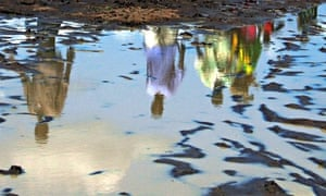 Sudanese are reflected in a pool of rain water in southern Sudan