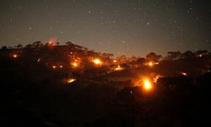 Small forest fires - pictured between pine trees at night at Sierra de Tejeda nature park, near the town of Competa, near Malaga