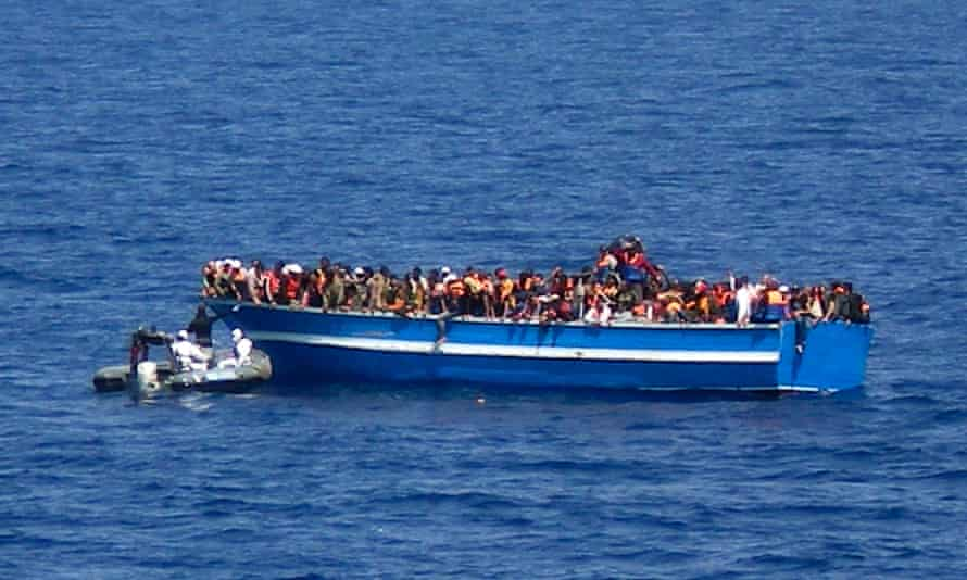 A motorboat of the Italian Navy approaches the boat of migrants in the Mediterranean Sea on Sunday 29 June