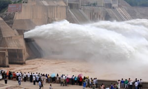 Tourists watching water gushing out from the Xiaolangdi Reservoir during a sand-washing operation in Luoyang, China