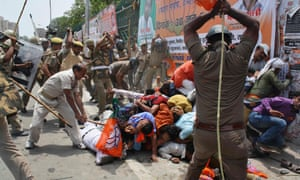 Indian policemen use batons to disperse youth wing workers of India's ruling Bharatiya Janata Party protesting outside the state assembly in Lucknow
