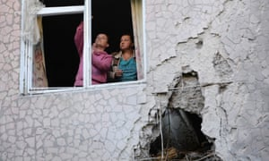People try to fix window shattered during shelling in Slaviansk, Donetsk region of Ukraine