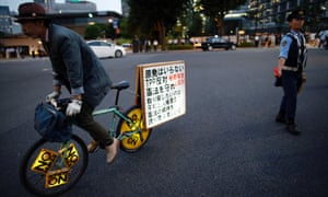Pacifist protestor rides a bicycle past a police officer standing guard - during a rally against Japan's Prime Minister Shinzo Abe