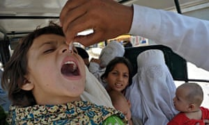 A health worker administers polio vaccination drops to a girl in a van in Bannu.