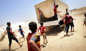 Desperate Iraqis at the Khazair displacement camp near Mosul, chase a Red Crescent society truck delivering food and other items