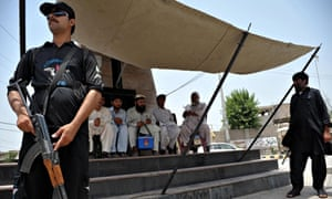 Police guard a polio vaccination team in Bannu