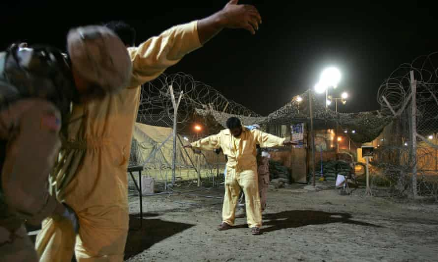 US army military policemen pat down suspected insurgents while processing new detainees at the Abu Ghraib in 2005.