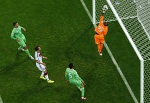 Algerian keeper Mbohli tips the ball over the bar.