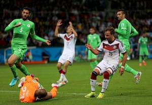 Goalkeeper Rais M'Bolhi of Algeria makes a double save from Toni Kroos and Mario Goetze.