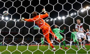 Andre Schuerrle of Germany scores his team's first goal past Algeria's 'keeper Rais M'Bolhi in extra time.