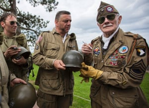 Belgian second world war veteran George Michels, who volunteered to join the US 326th Airborne and fought in the Battle of the Bulge, (R) signs the helmets of second world war enthusiasts in the US cemetery in Colleville-Sur-Mer, in Normandy, France.