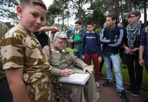US second world war veteran George Shenkle from Pennsylvania, who fought in E Company, 2nd Battalion, 508th Parachute Infantry Regiment, 82nd Airborne Division, signs autographs for school children at the US cemetery in Colleville-Sur-Mer, in Normandy, France.