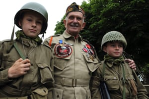 US second world war veteran Jack W Schlegel (L), 91 years-old from Mount Tremper, New York, who served with the 508 PIR, 82nd Airborne, poses with British youths from Yorkshire, Cameron Stevens (R) and Joe Newton in Sainte-Marie-du-Mont. Schlegel parachuted onto the Normandy coast in the early hours of June 6, 1944.