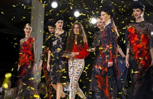 Grace Weller flanked by models wearing her designs at Graduate fashion week.