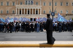 A Greek orthodox priest looks on as Golden Dawn supporters hold Greek flags during a rally outside Parliament in Athens, Wednesday, June 4, 2014.
