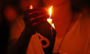 A woman holds a candle as tens of thousands of people attend a candlelight vigil at Victoria Park in Hong Kong