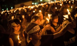 People take part in a candlelight vigil during heavy rain in Hong Kong.