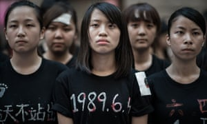 Students look on before singing to commemorate China's 1989 Tiananmen Square.