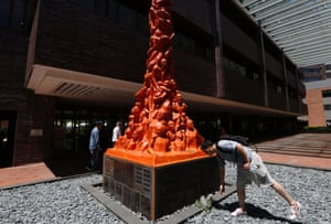 """A man places flowers at the """"Pillar of Shame"""" statue, which commemorates the June 4, 1989 military crackdown on a pro-democracy student movement, in the University of Hong Kong."""