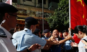 Police stop a pro-China protester carrying a Chinese flag as he attempts to approach anti-Chinese demonstrators during a rally near Hong Kong's Victoria Park.