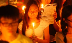 A woman closes her eyes as she joins tens of thousands of people attending a candlelight vigil at Victoria Park.