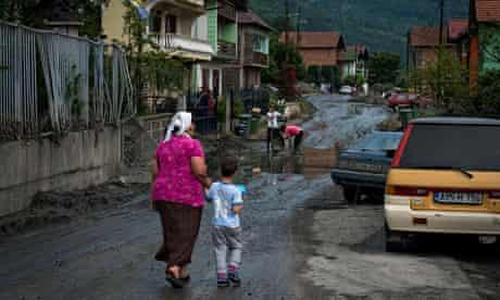 A woman leads a child wearing a football shirt bearing Edin Džeko's name through a flood-hit settlem