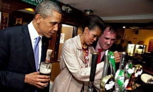 Barack Obama watches Michelle draw a pint at Ollie Hayes' Pub in Moneygall, Ireland. Photograph: Rex