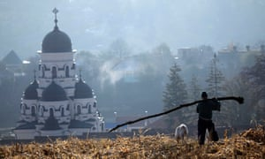 A Moldovan farm worker carries the trunk of a fallen tree through the corn fields in front of the Capriana monastery in Capriana, in 2011.