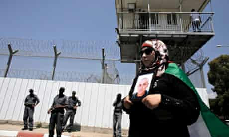 A Palestinian woman holds a picture of a man jailed in an Israeli prison