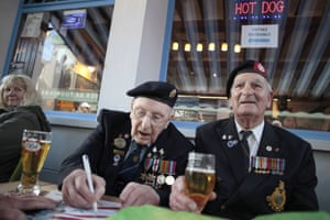 British second world war veterans, Army veteran Ronald Penglase (L) and Navy veteran Dennis Stuthridge (R), share a beer in Arromanches-les-Bains, northwestern France.