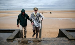 Second world war veteran Charles Alford of the 6th Armor Division, from Waco, Texas, climbs the stairs with his son David on Omaha Beach where he landed as part of the invasion of Normandy.