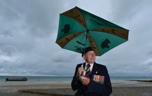 British D-day veteran Harry Mason, 95, formerly of the Royal Medicals Corps, from Warrington braves the wet and windy weather at Arromanches-les-Bains on the Normandy coast.