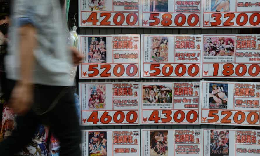A man walks past advertisements for explicit animation DVDs in Tokyo.