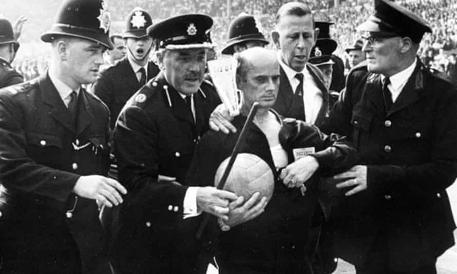 West German referee Kreitlin is escorted off the pitch by policemen at the end of this World Cup quarter final match after he had sent off Argentine captain Rattin.