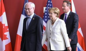 European Council president Herman Van Rompuy, German chancellor Angela Merkel and David Cameron walk past national flags during the second day of the G7 summit in Belgium