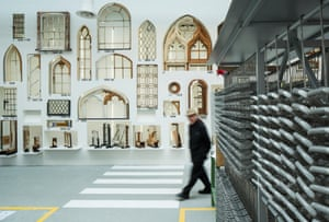 A visitor walks in front of a collection of windows from the Brooking National Collection. On the right is a section of the Sobinco window factory that has been imported from Belgium. Window is one of 17 rooms that collectively form 'elements of architecture' inside the Central Pavilion at the Giardini.