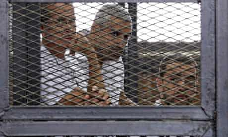 Al-Jazeera journalists Peter Greste, Mohamed Fahmy and Baher Mohamed behind bars at a court in Cairo