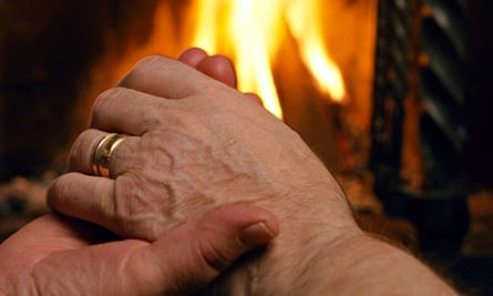 An old couple sitting hand in hand by the fireplace. Image shot 2006. Exact date unknown.